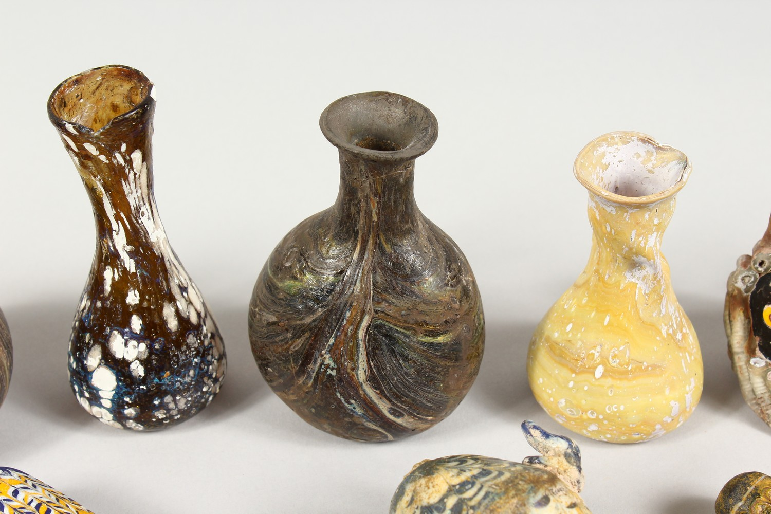 A GROUP OF THIRTEEN ROMAN GLASS BOTTLES AND JARS, including three tops in the form of heads (13). - Image 3 of 11