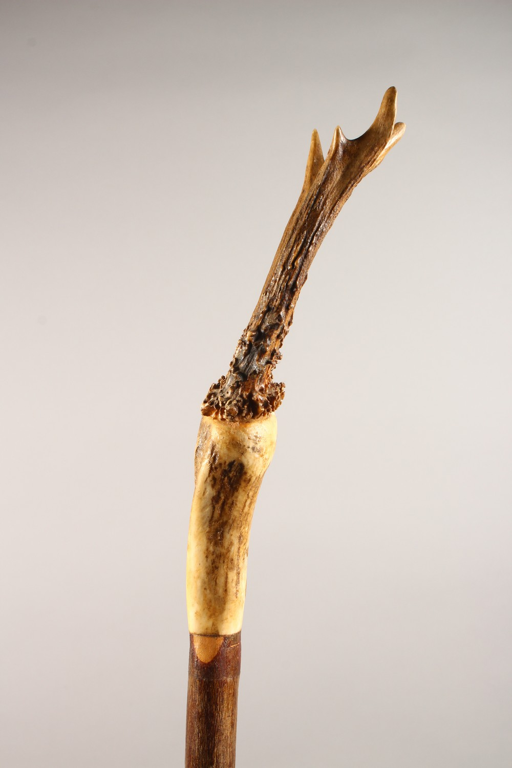 Lot 1521 - A THUMB STICK, with antler handle. 58ins long.