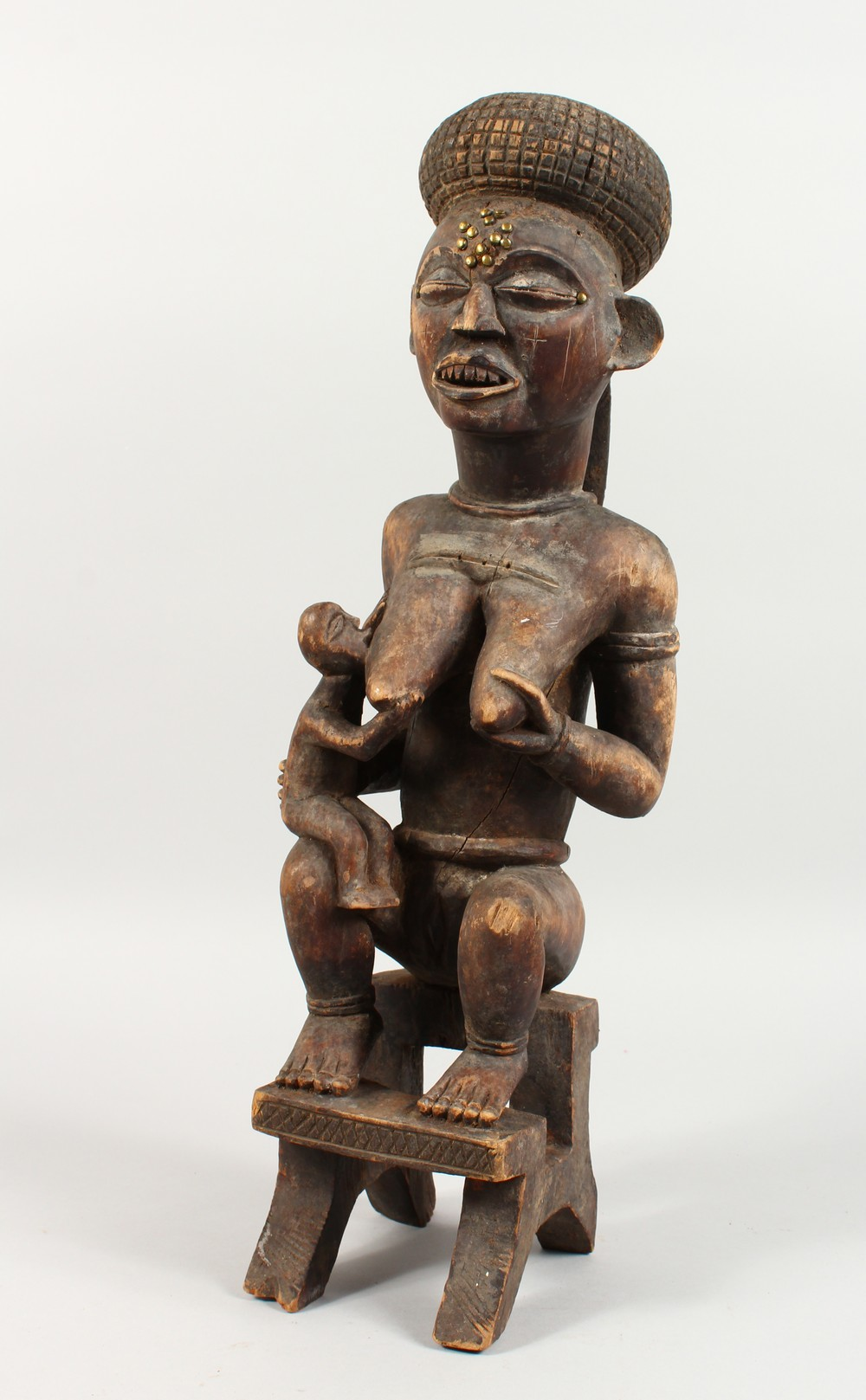 A LARGE CARVED WOOD TRIBAL FIGURE, mother and child seated on a stool. 21.5ins high.