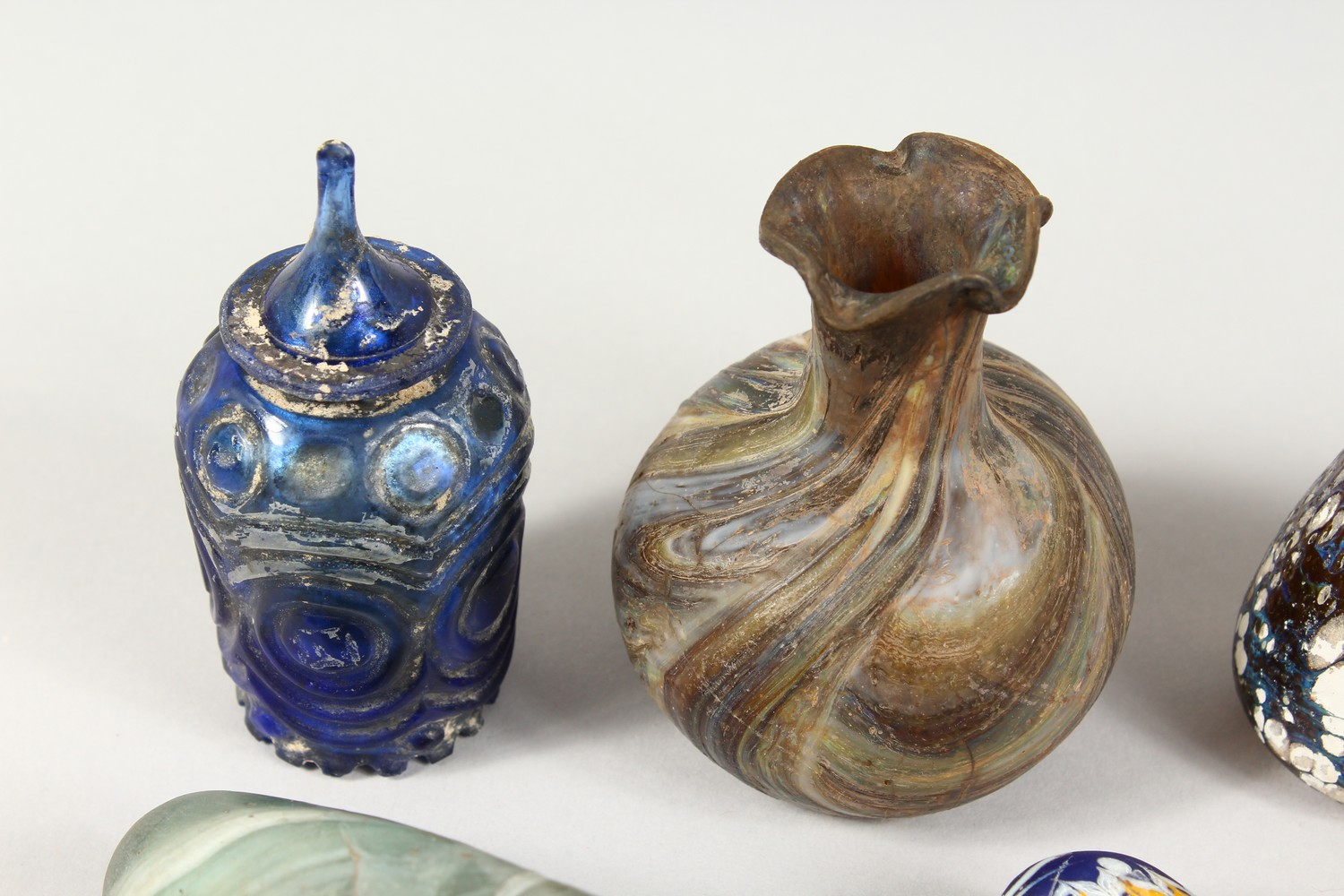 A GROUP OF THIRTEEN ROMAN GLASS BOTTLES AND JARS, including three tops in the form of heads (13). - Image 2 of 11