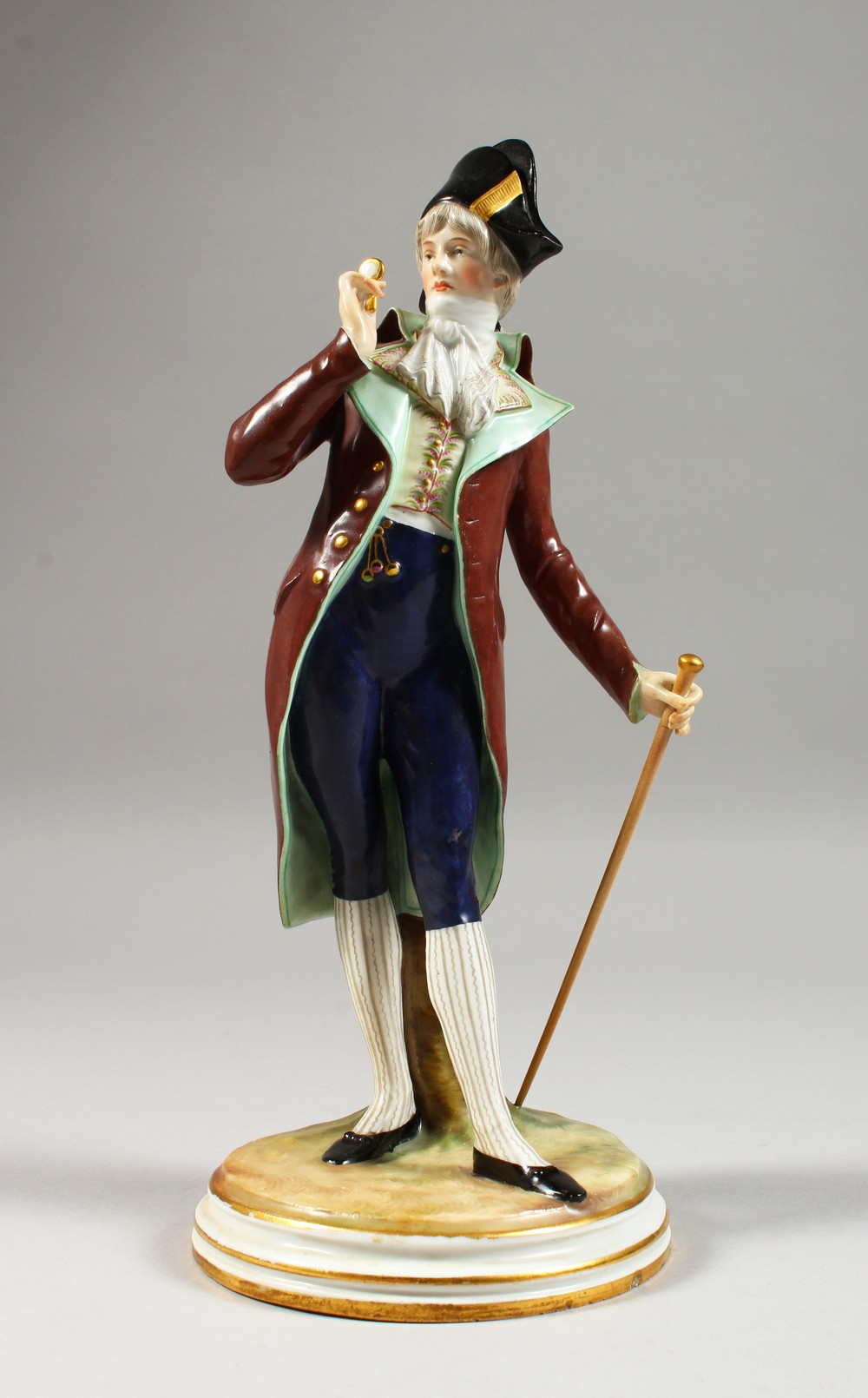 A MEISSEN FIGURE OF A DANDY, standing wearing a tailcoat, a stick in his left hand, a monocle in his