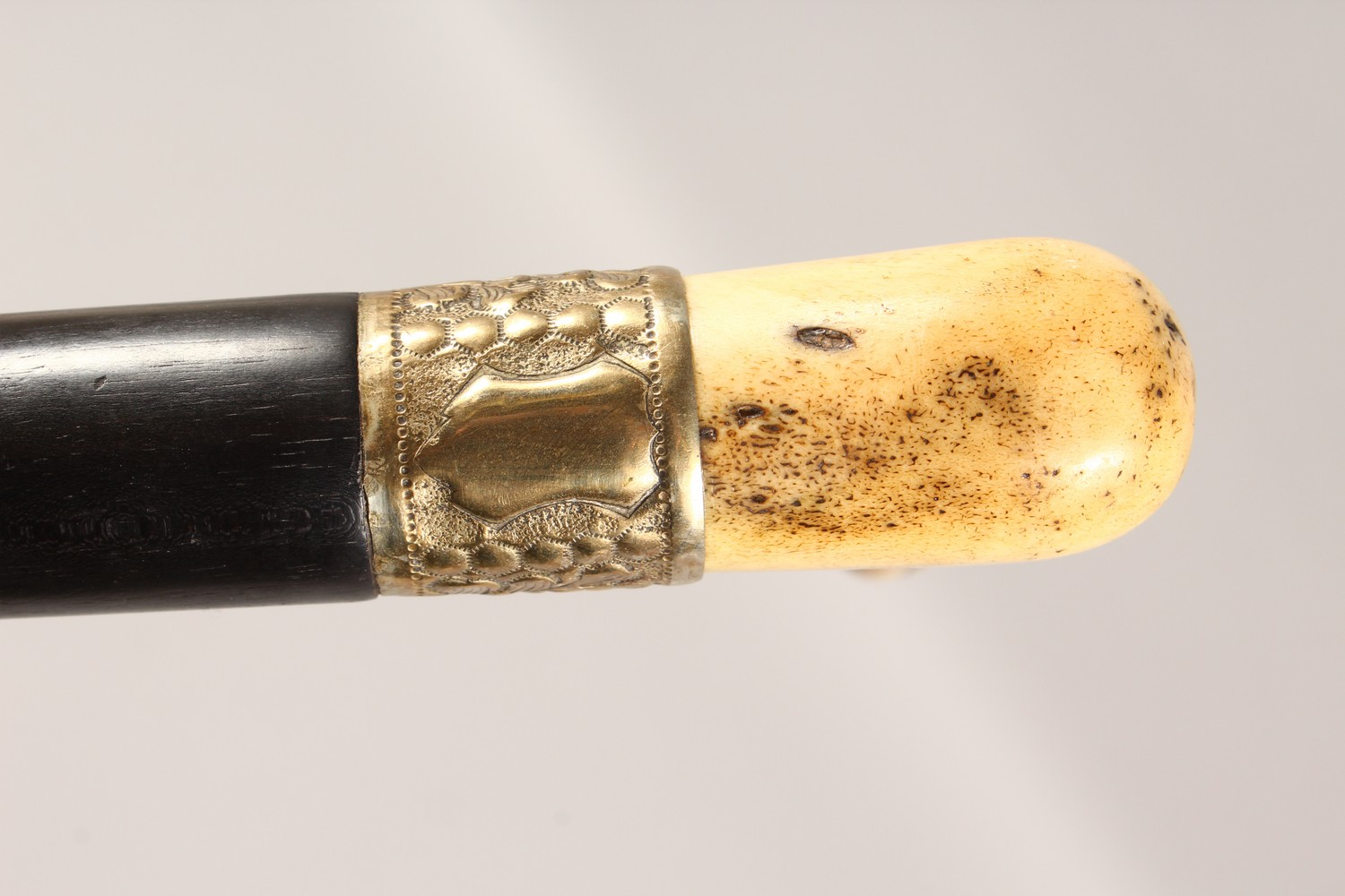 Lot 1527 - AN ANTLER HANDLED WALKING STICK, with embossed metal collar and ebony shaft. 36ins long.