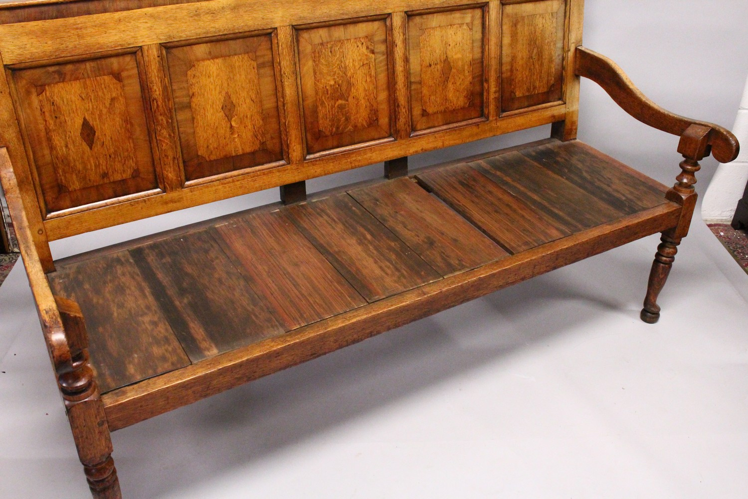 AN 18TH CENTURY OAK PANEL BACK SETTLE, with five mahogany banded panels, loose cushion, on turned - Image 5 of 6