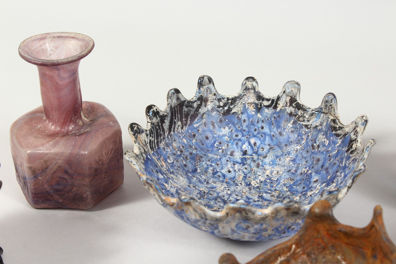 Lot 1294 - A COLLECTION OF ROMAN GLASS BOWLS AND JARS, models of birds and animals and a tortoise shaped