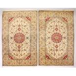 A PAIR OF PERSIAN TABRIZ CARPETS, beige ground with a central medallion and floral decoration (