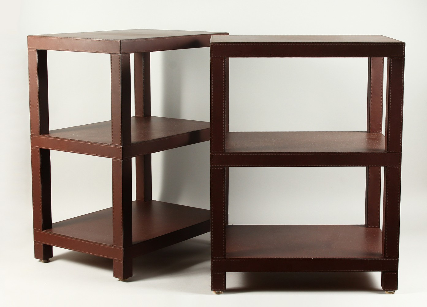 DOMINIC CHAMBON, A GOOD PAIR OF LEATHER COVERED THREE TIER OCCASIONAL TABLES. 48cms wide x 34cms