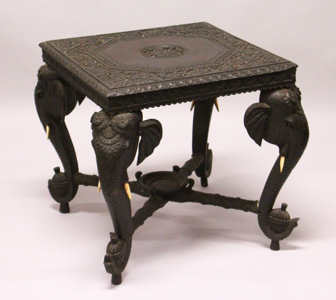 AN EARLY 20TH CENTURY CEYLONESE CARVED EBONY LOW TABLE, with an elephant head leg to each corner.