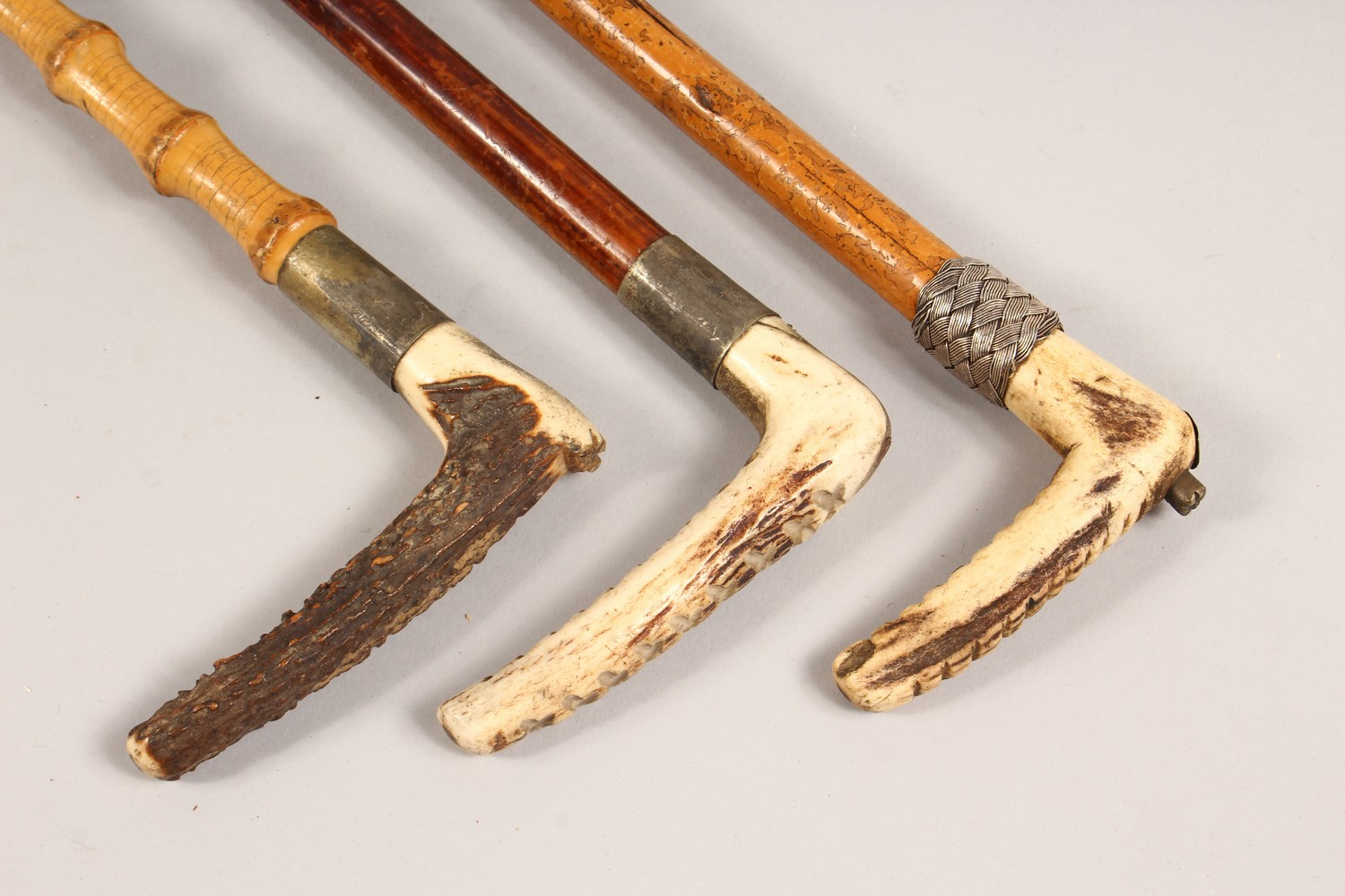 Lot 1529 - THREE ANTLER HANDLED RIDING CROPS.