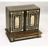 AN IVORY INLAID EBONY TABLE CABINET, the pair of doors inlaid with ached panels decorated with