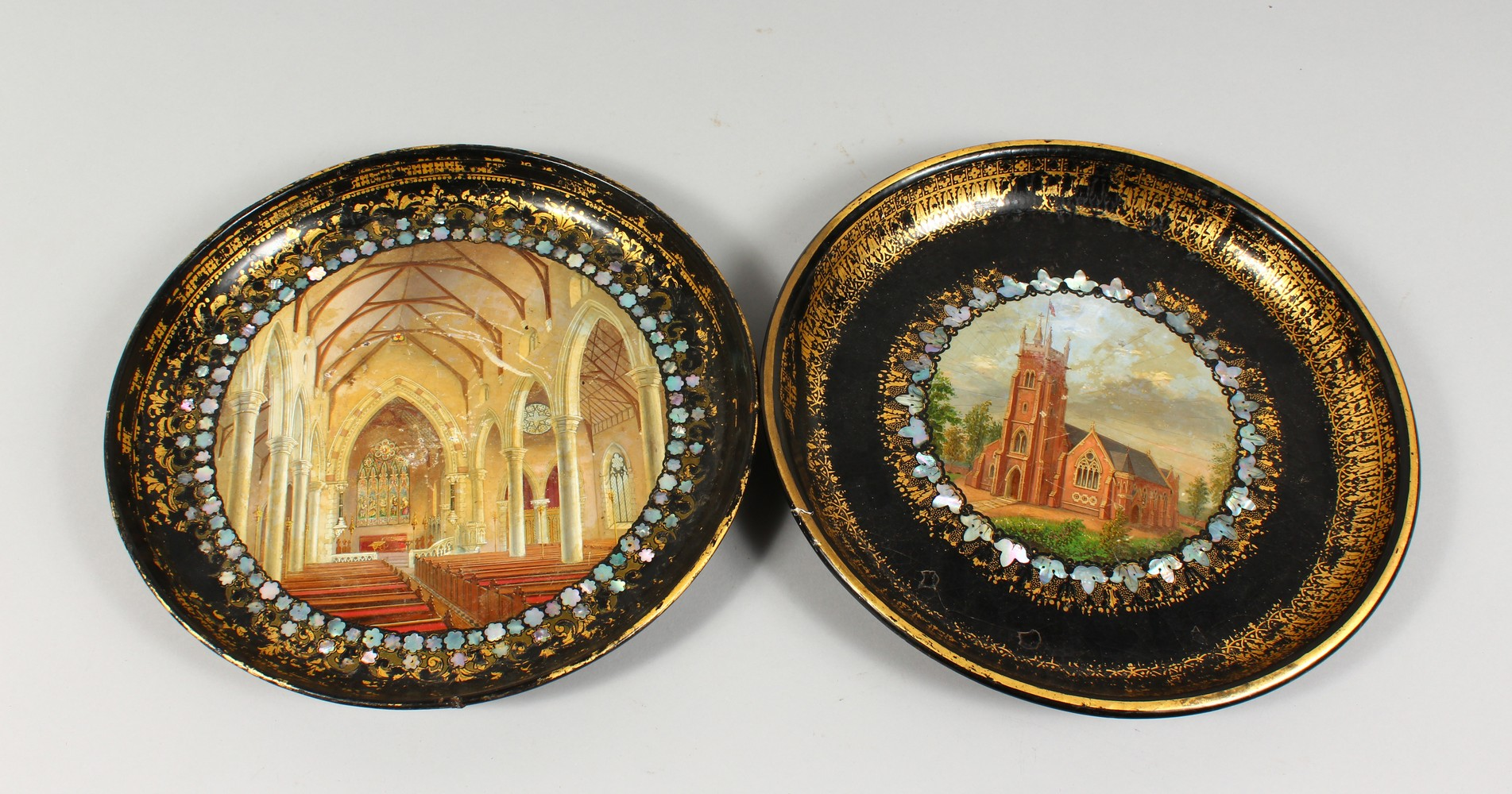 Lot 1395 - TWO VICTORIAN CIRCULAR PAPIER MACHE TRAYS, decorated with a church exterior and interior. 12ins