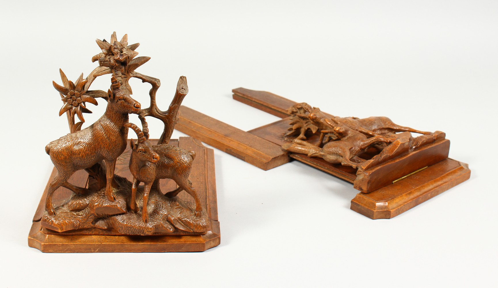 A GOOD PAIR OF BLACK FOREST CARVED WALNUT ADJUSTABLE BOOK RESTS, carved with goats. Each 10.75ins
