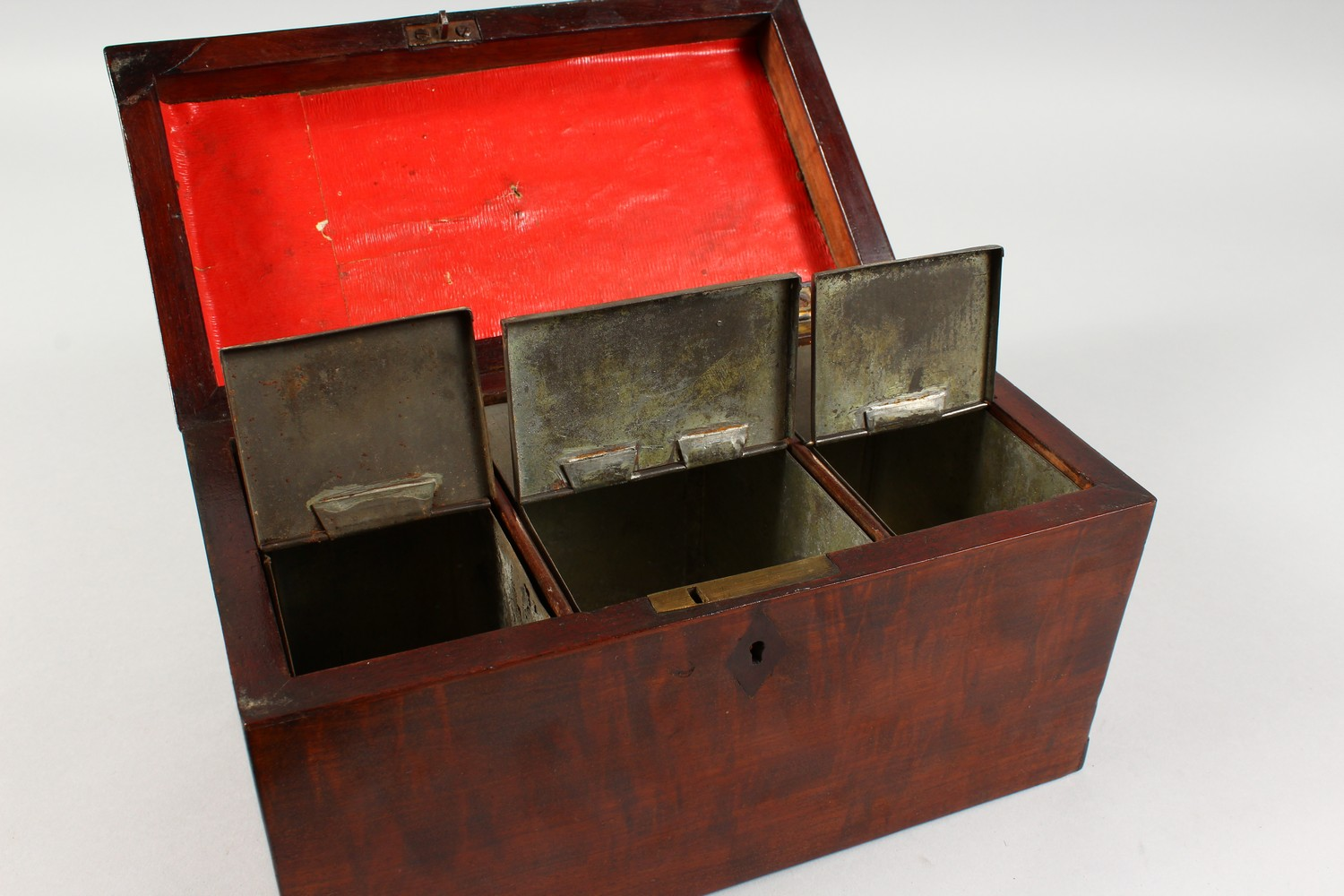 Lot 1484 - A GEORGE III MAHOGANY TEA CADDY, with brass carrying handle and three division interior with tins.