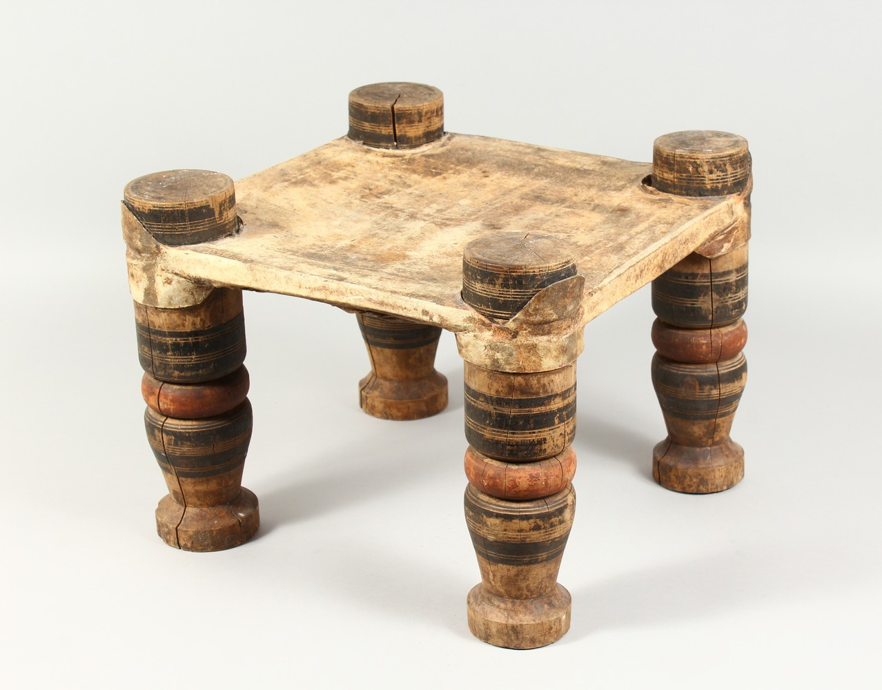 A NORTH AFRICAN PAINTED WOOD AND ANIMAL SKIN SQUARE SHAPED STOOL. 15ins wide x 11.5ins high.