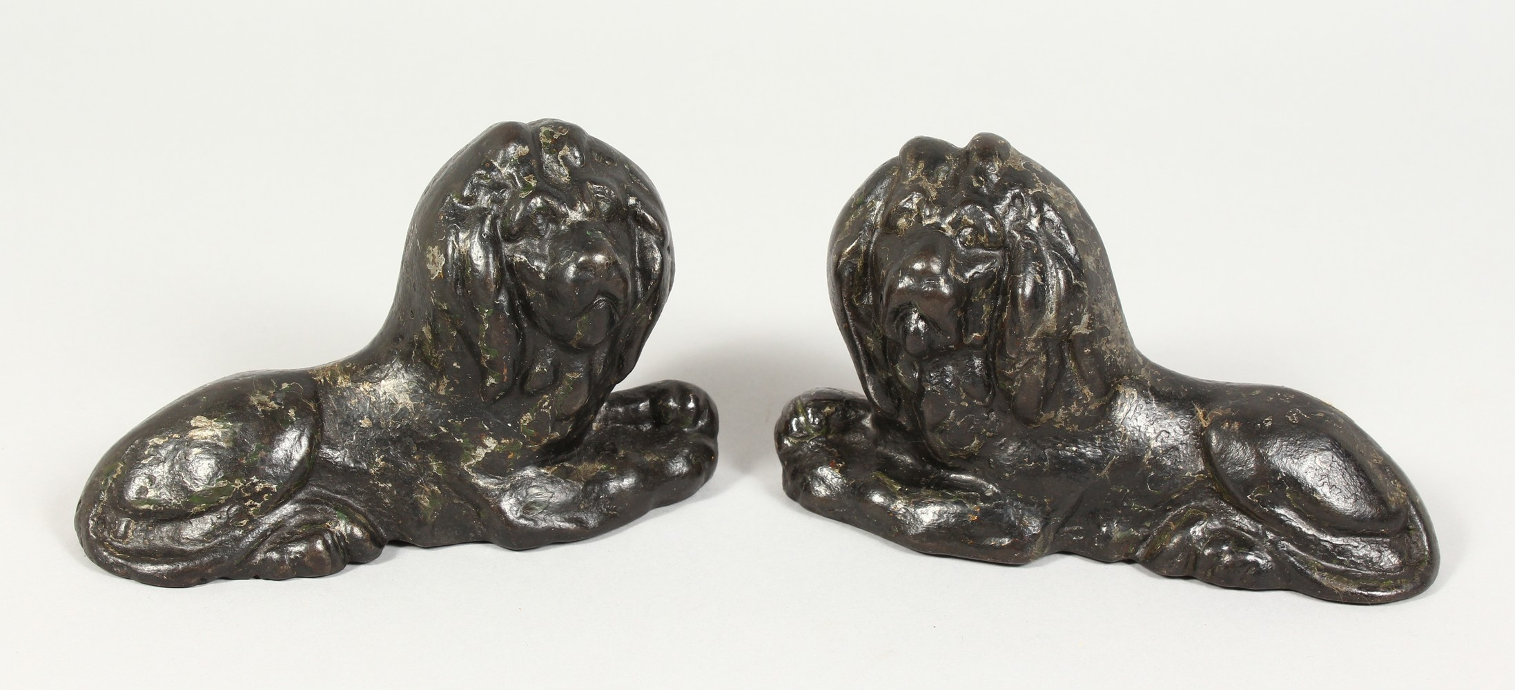 Lot 1358 - A PAIR OF 19TH CENTURY SMALL CAST IRON MODELS OF LIONS. 6ins long.