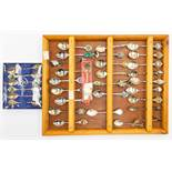 A collection of plate/EPNS/chromed and white metal souvenir spoons, on modern mount frame with a