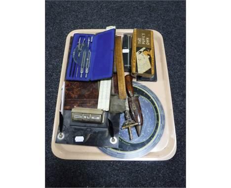 A tray containing calendar desk stand, drawing utencils, Parker pens, miniature rapier, vintage slide rule, Planisphere etc