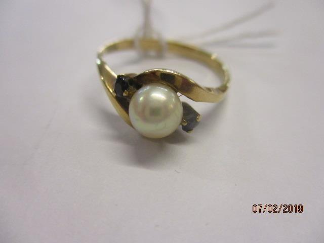 Lot 14 - A yellow metal ring set with a central pearl flanked by two small sapphires, marks rubbed, total
