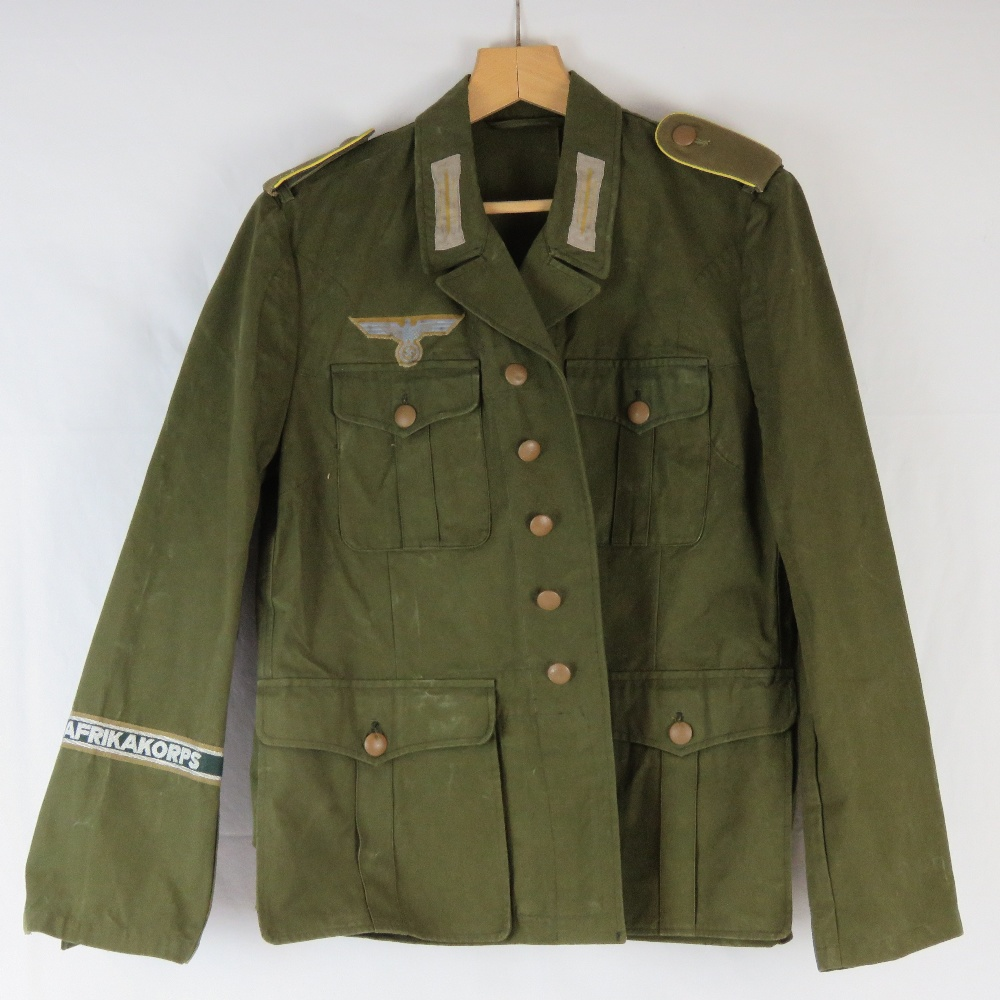 A WWII German Afrika Korps tunic complete with cuff title and cloth badges.