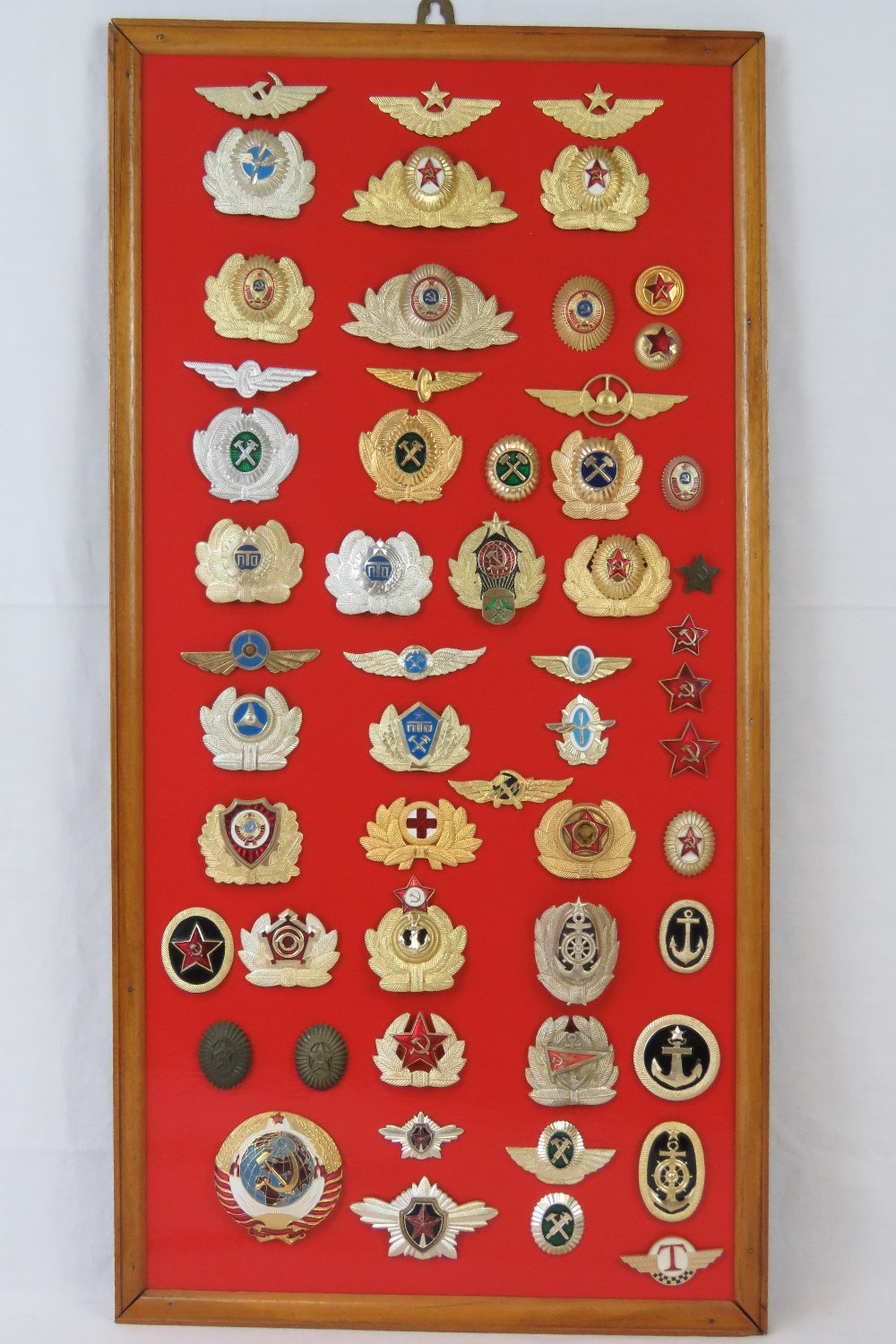A collection of Russian USSR badges mounted on board, fifty-five items.