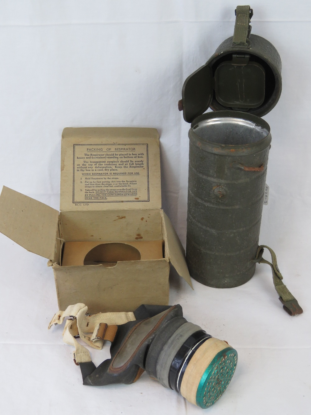 A German cylindrical gas mask cannister, together with a British WWII childs gas mask,