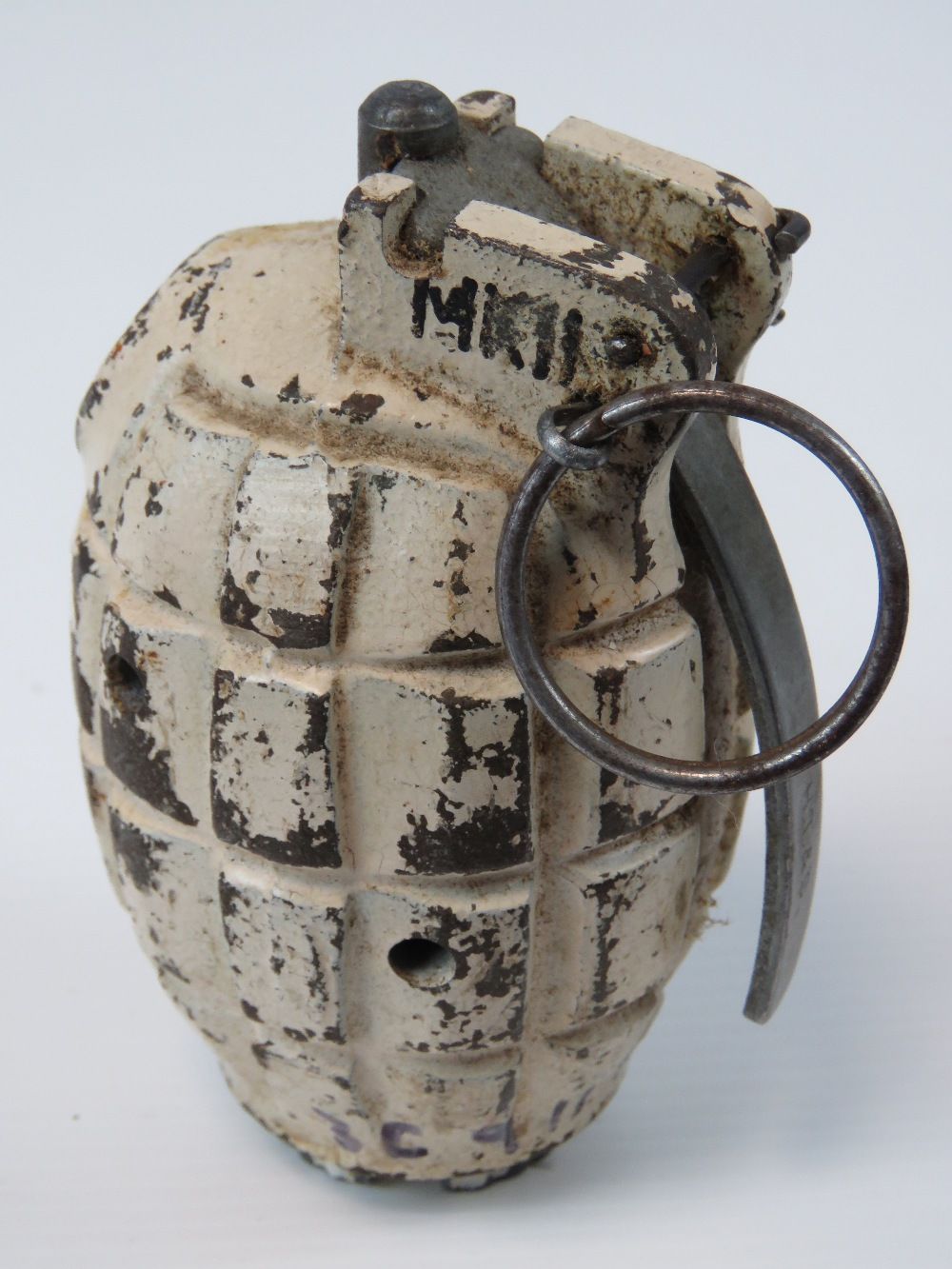 An inert British WWII Mk2 Mills grenade, painted in Artic /Winter camouflage, fuse plug dated 1945.