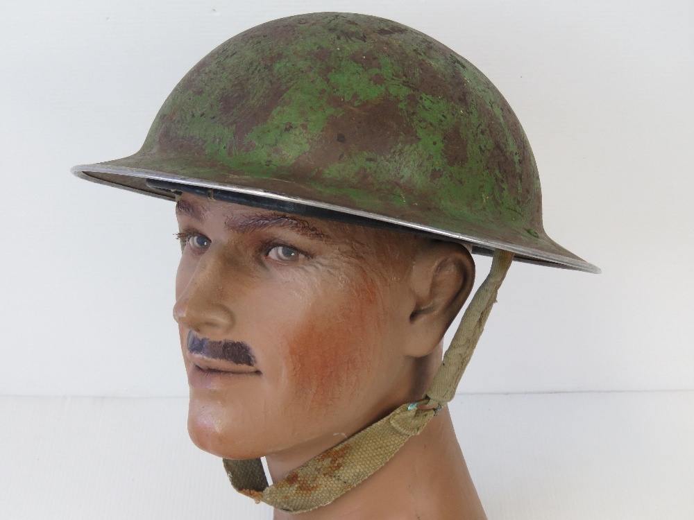 A WWII British military issue helmet, dated 1940 with original liner and chinstrap.
