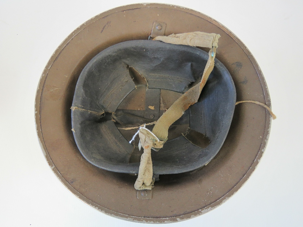 A WWII British military issue helmet, dated 1940 with original liner and chinstrap. - Image 2 of 3