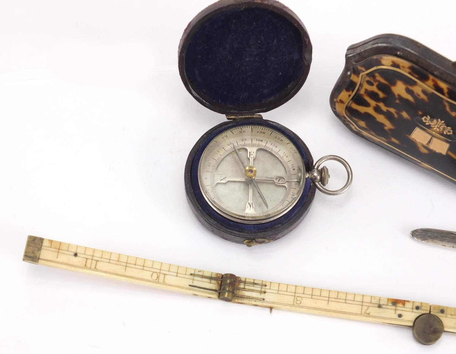 Lot 34 - Antique objects comprising a pocket compass with leather case, folding ivory rule, silver bladed