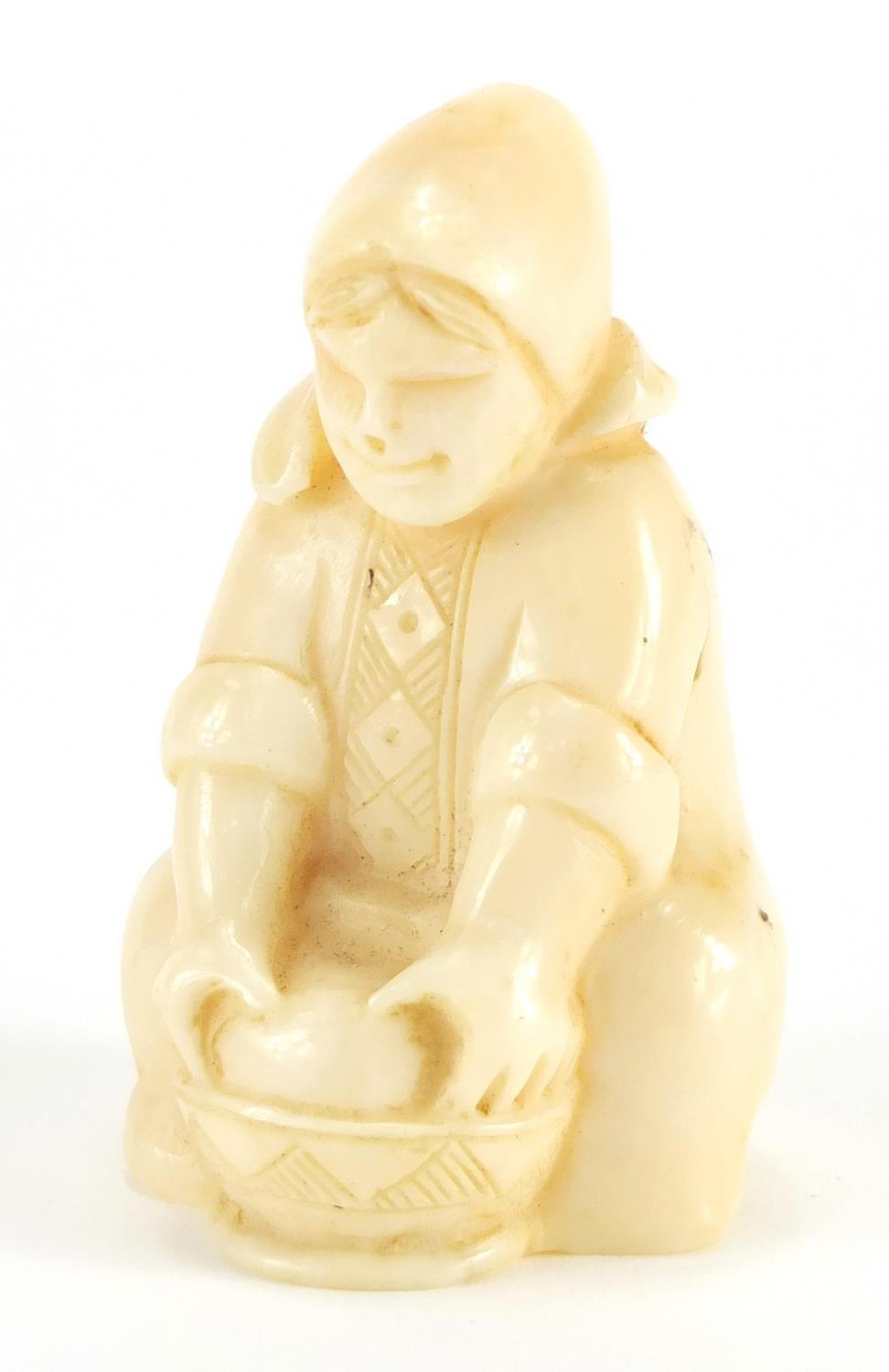 Lot 55 - Dieppe carved ivory figure of a young girl washing, incised numbers to the base, 6.5cm high :For