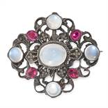 AN ANTIQUE MOONSTONE AND PASTE BROOCH in silver, the open scrolling face set with five round