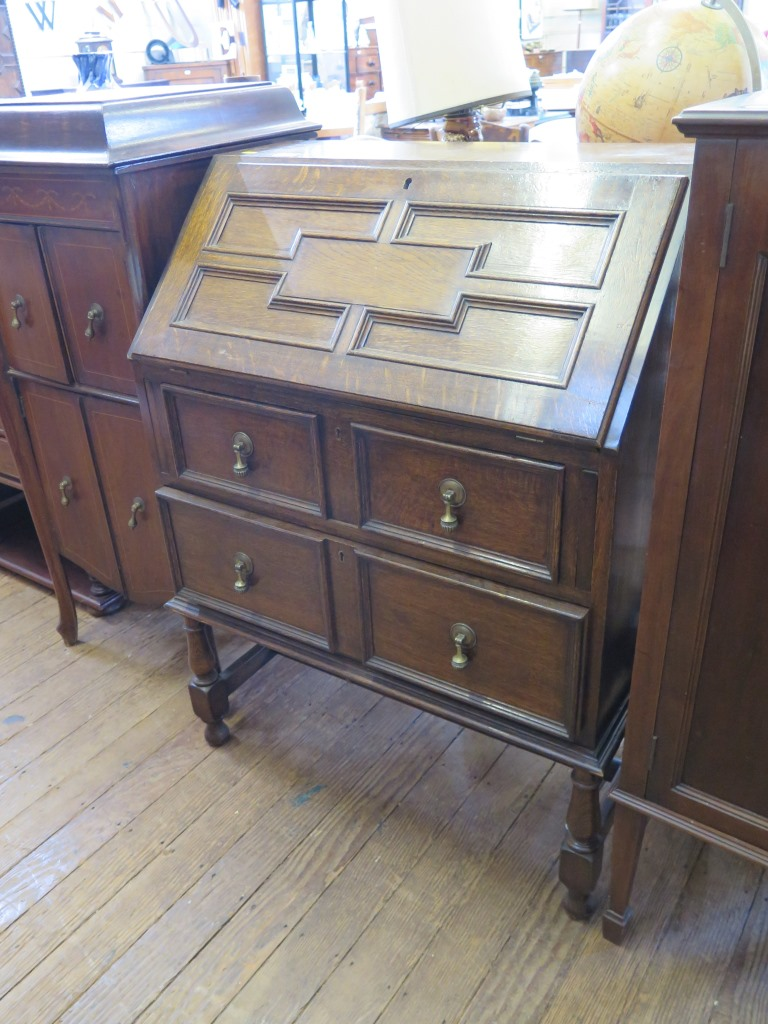 Lot 5 - An 1930s oak bureau, the panelled slope enclosing pigeonholes over two graduated drawers on turned