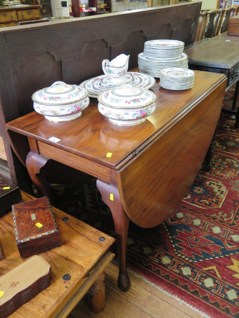 Lot 55 - A mahogany George III style drop leaf table, the oval top on cabriole legs and club feet, 104cm