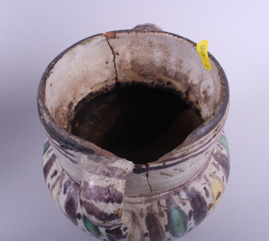 "Lot 31 - A North African slip decorated two-handled jar, 12"" high, (surface cracking), a similar jar ("