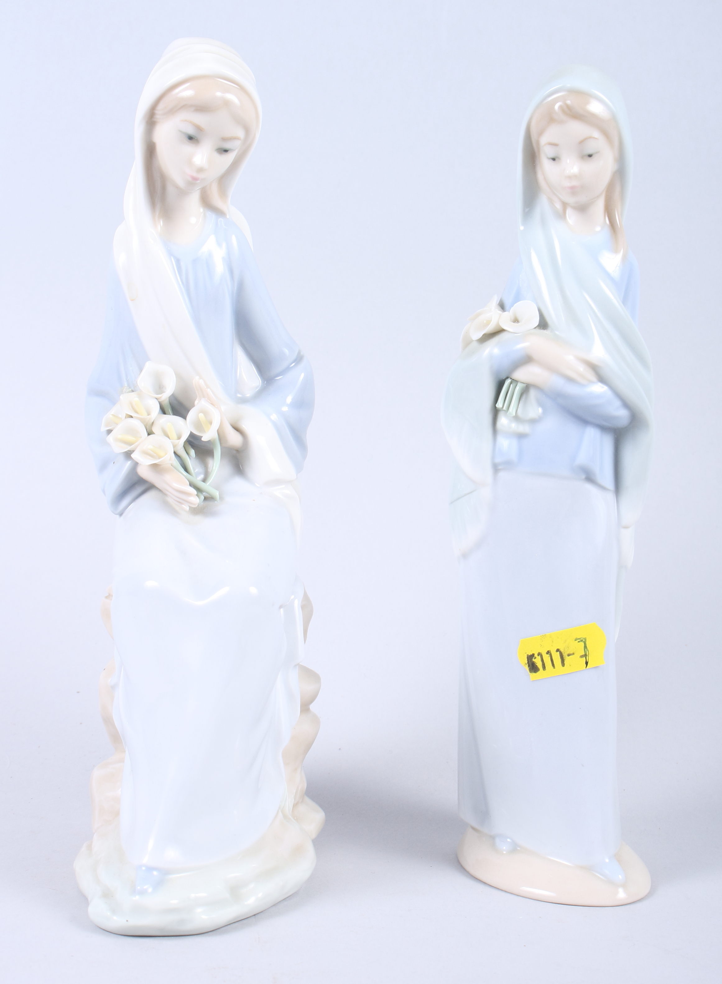 """Lot 7 - A Lladro figure of a woman holding lilies, 9"""" high, and a Lladro figure of a seated girl with"""