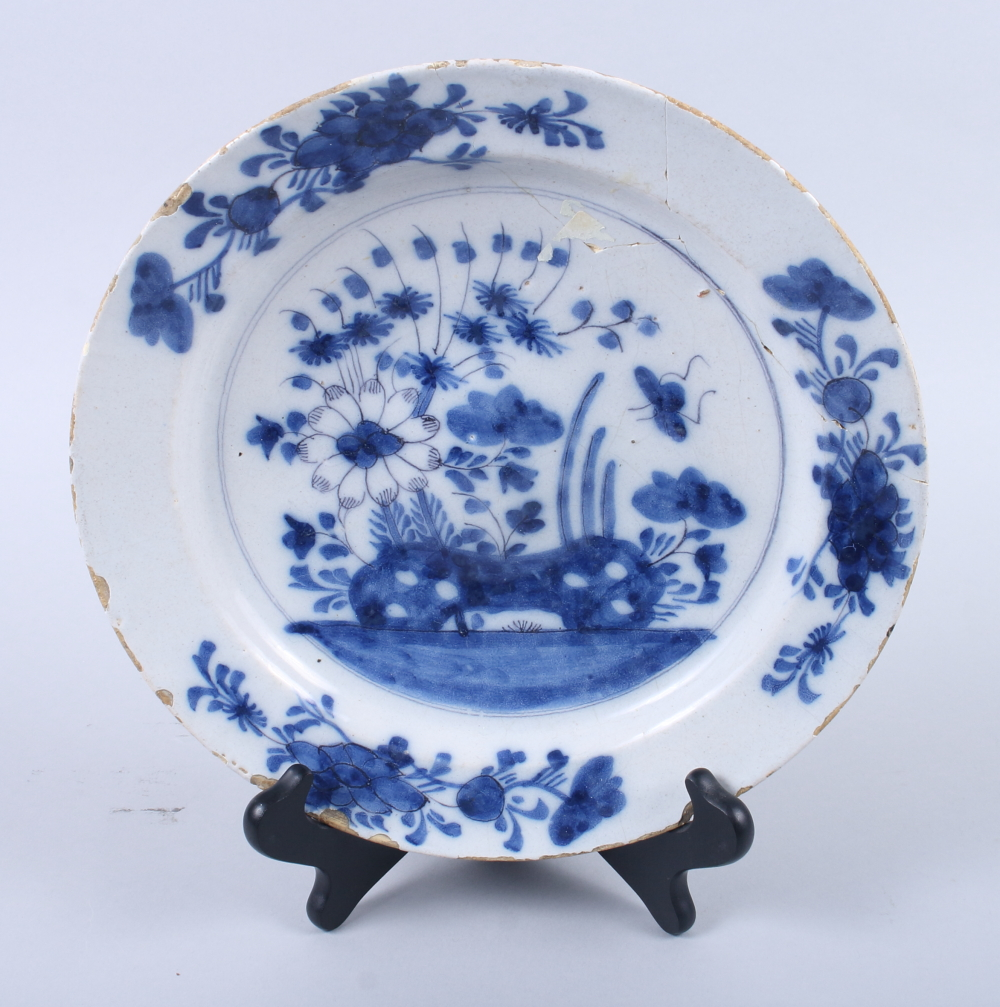 """Lot 25 - An English delft blue and white plate, decorated with insects, root and plant, 10"""" dia (rim"""
