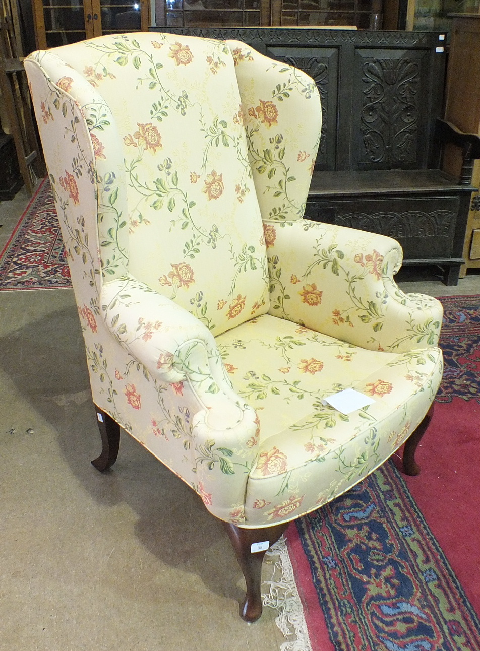 Lot 35 - Four modern 'Duresta' floral-decorated wing armchairs raised on stained wood cabriole legs, (