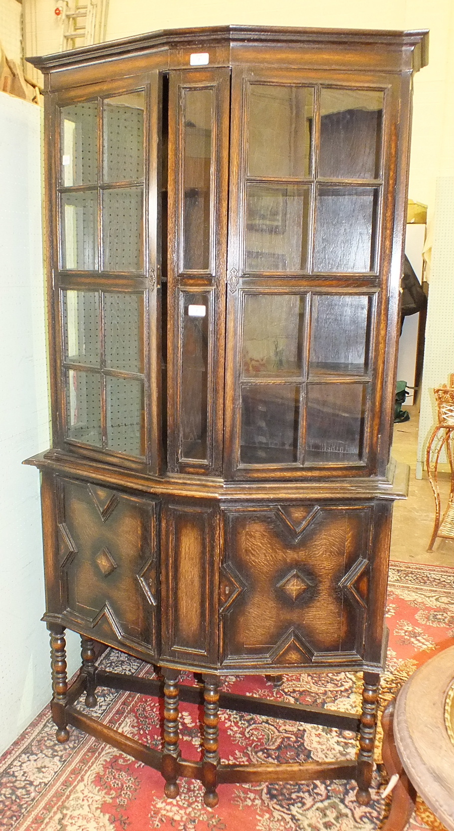 Lot 7 - A mid-20th century bowed oak bookcase, the shelved upper section fitted with a pair of astragal-