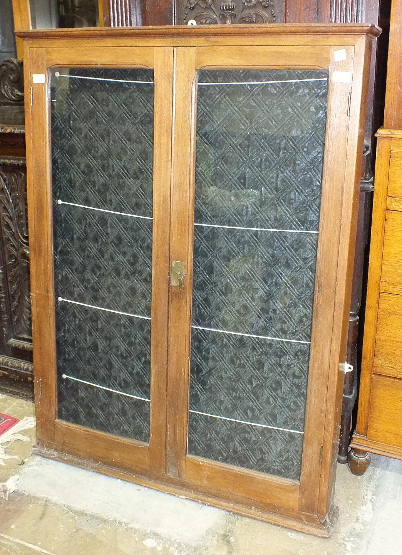 Lot 49 - An Edwardian teak display notice board having a pair of glazed doors, 125cm high, 96cm wide.