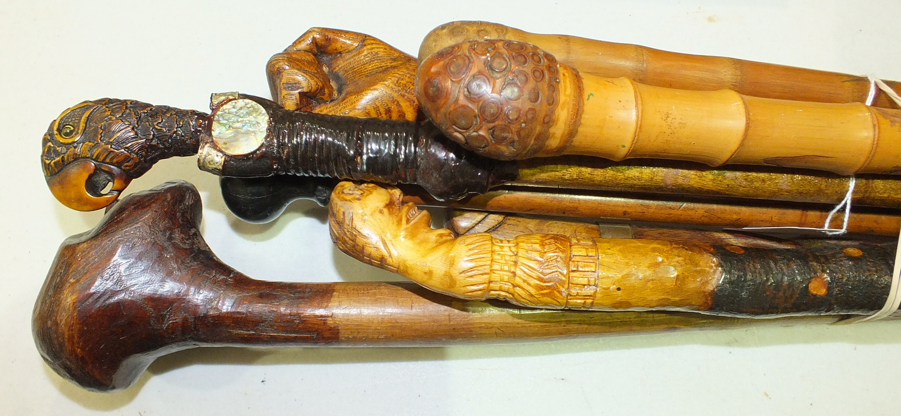 Lot 129 - Two carved bamboo walking sticks and five others, (7).