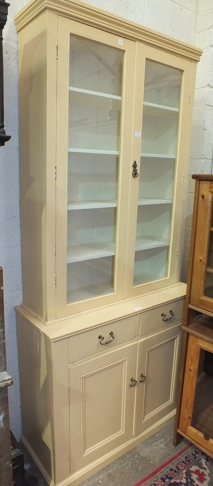 Lot 23 - A late-19th/early-20th century painted pine bookcase, the upper section fitted with a pair of glazed