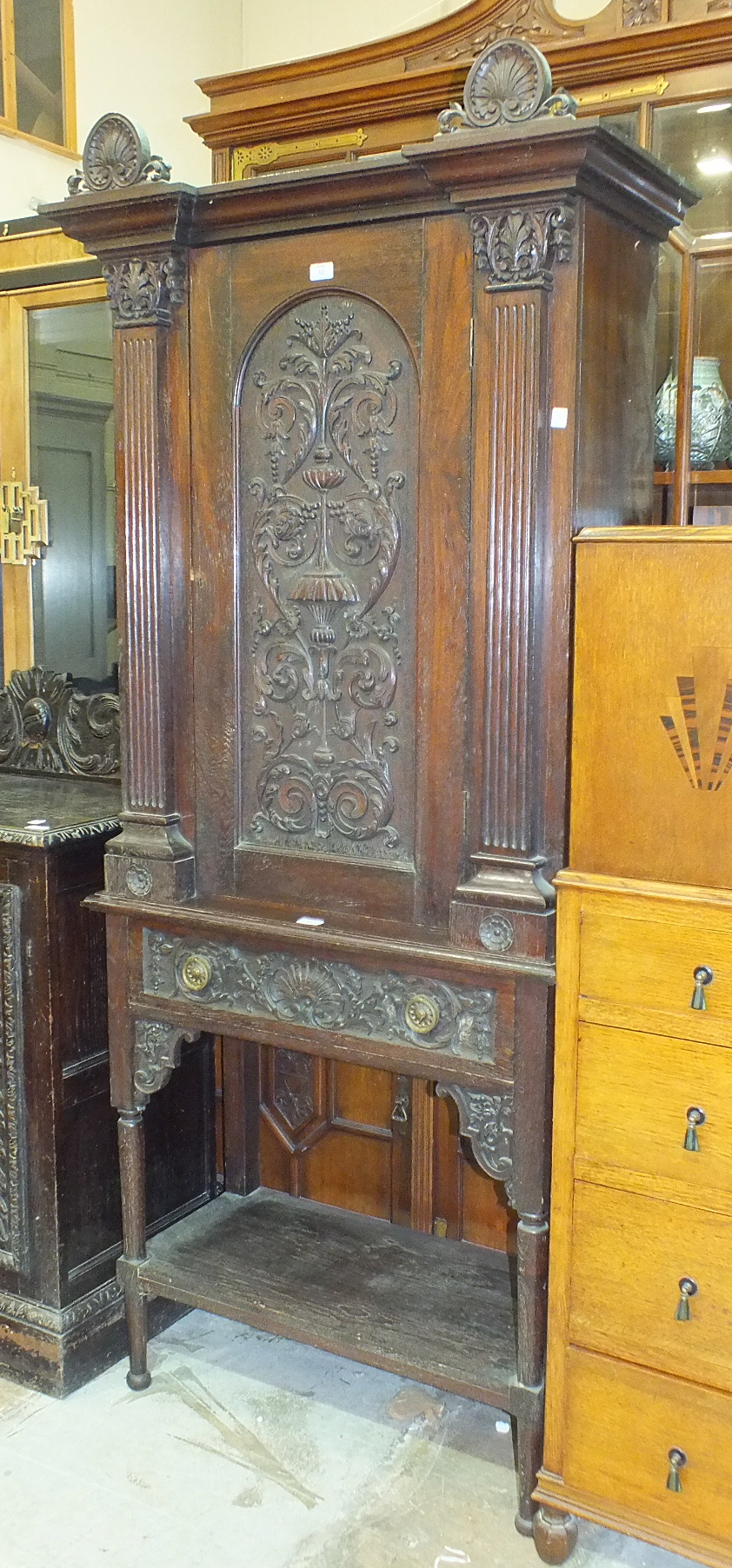 Lot 12 - A Continental carved oak side cupboard having a single carved door above a drawer, on turned legs,