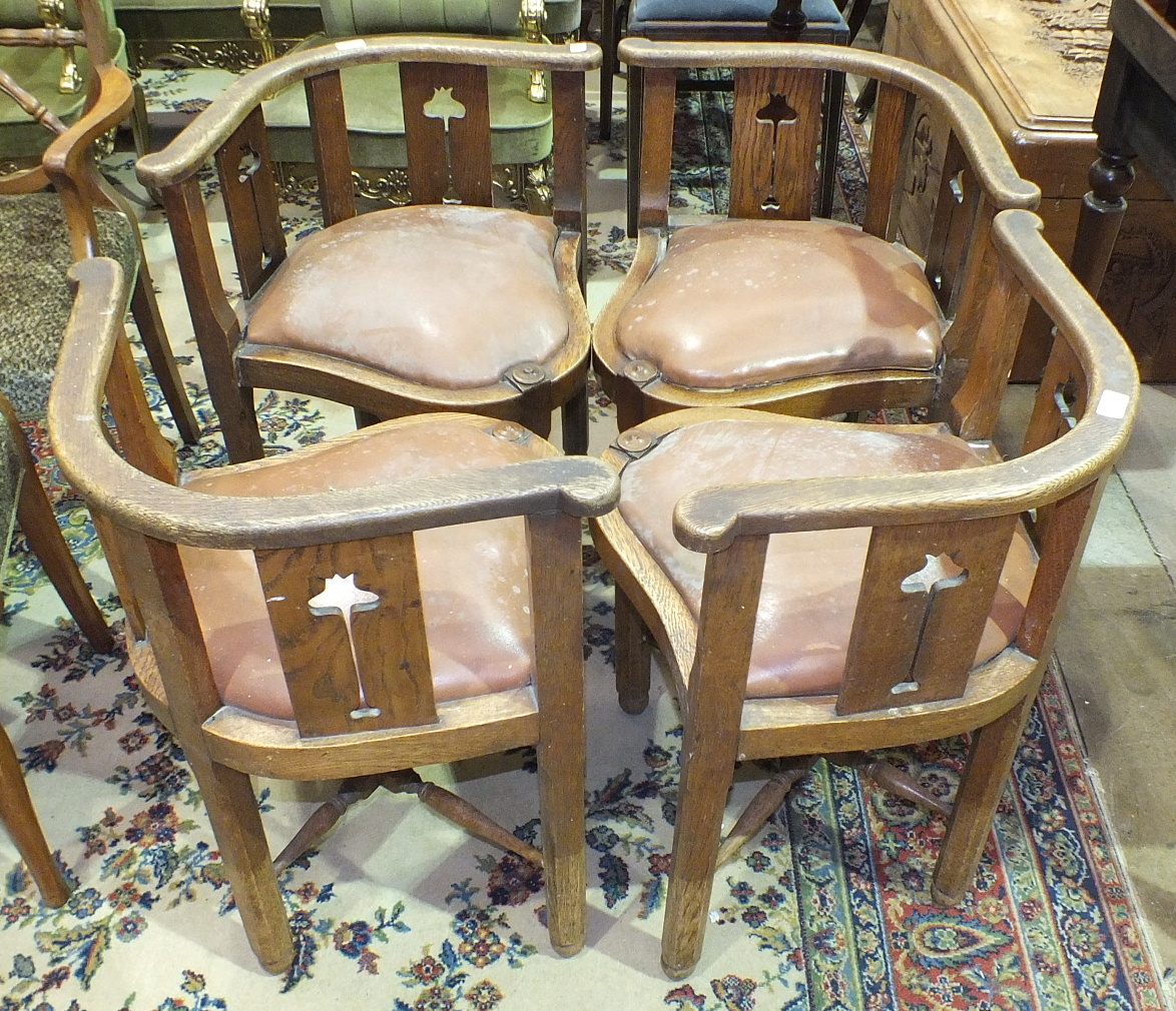 Lot 25 - A set of four Edwardian oak corner chairs with low bowed backs, pierced Art Nouveau-style floral