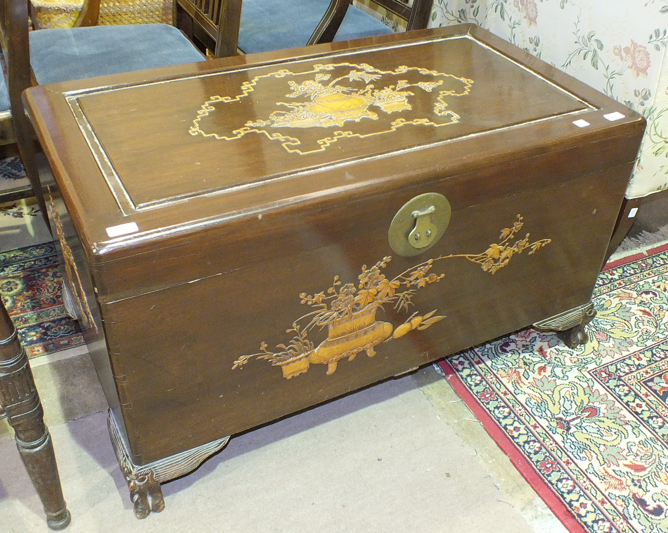 Lot 27 - A mid-20th century camphor wood chest with carved sides and lid depicting vases of flowers, 100cm