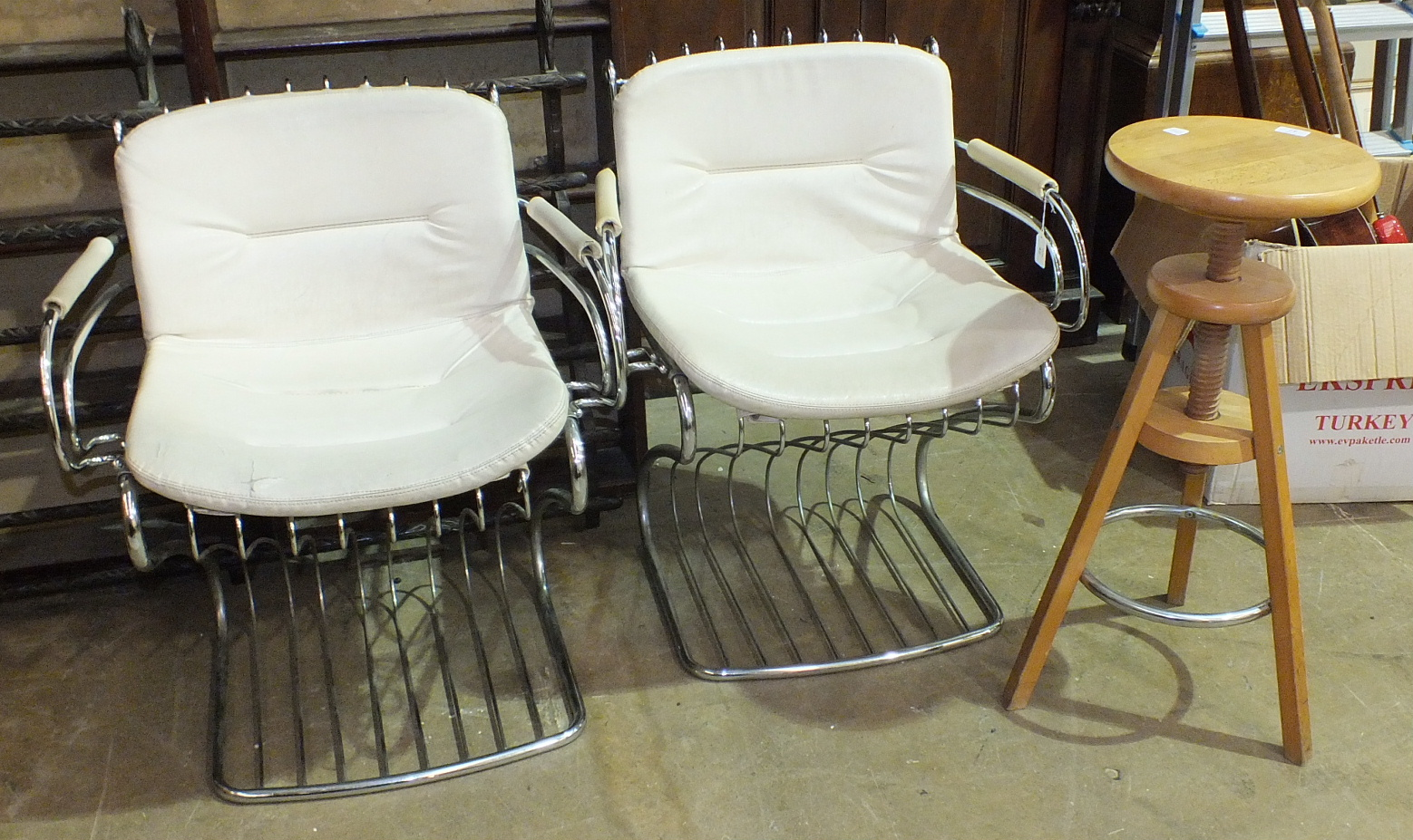 Lot 42 - A pair of chrome-framed armchairs with white Rexine seats and backs, (some damage to seats) and an