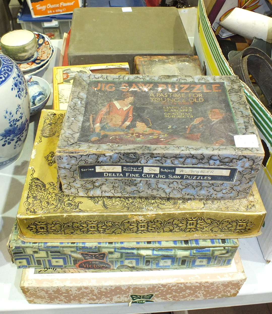An olive wood games counter, a small collection of jigsaw puzzles and other items.