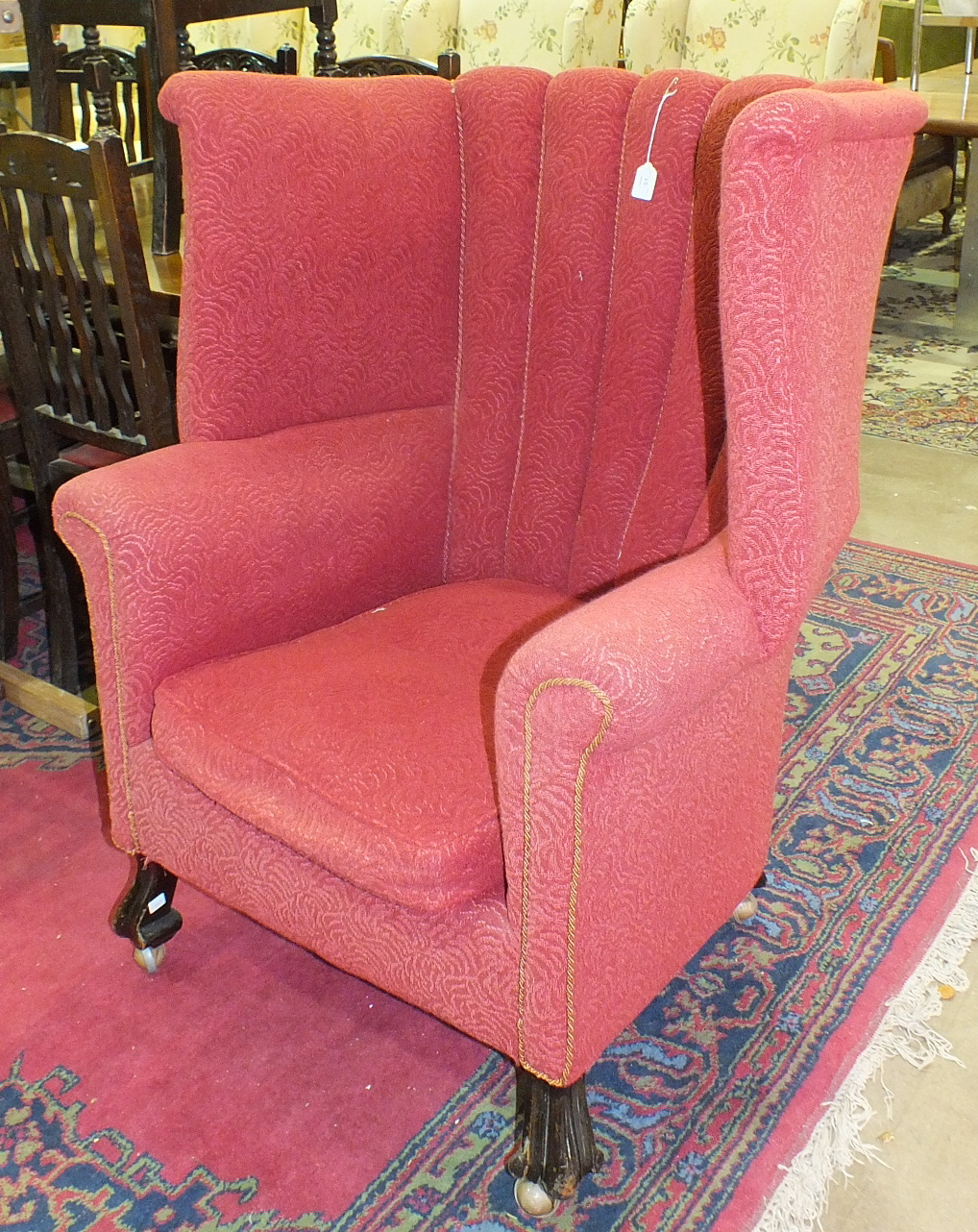 A large upholstered winged tub armchair on carved wood feet.