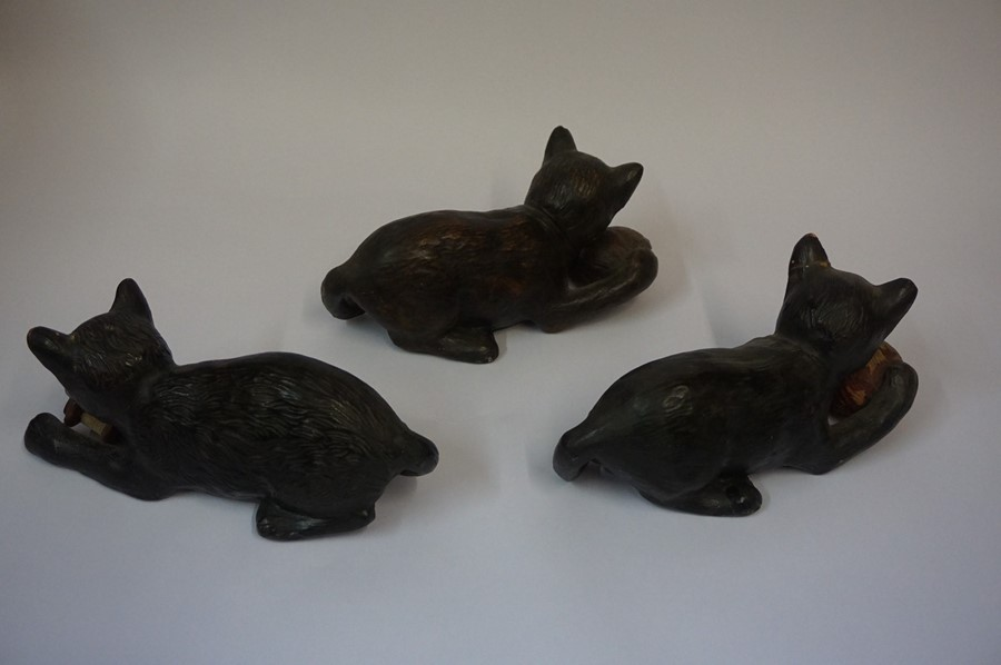 Lot 79 - Three Similar Bretby Terracotta Cat figures, each figure having glass eyes and holding a ball,
