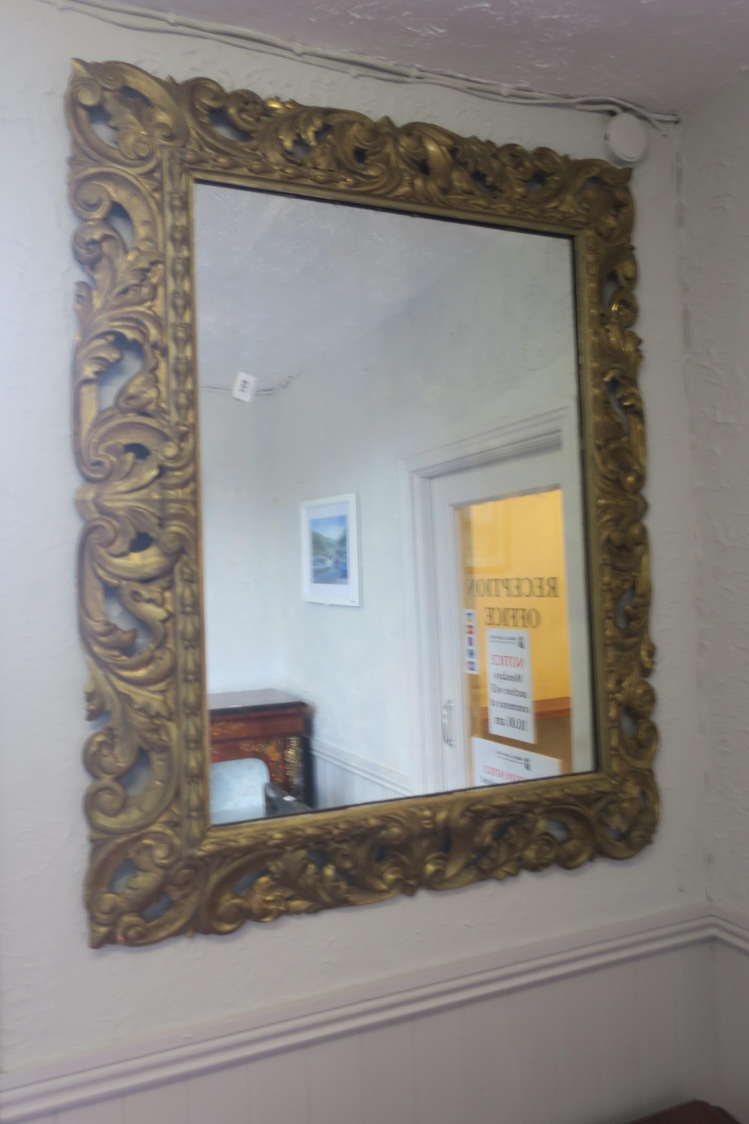 Lot 392 - A 19TH CENTURY CARVED GILTWOOD MIRROR the rectangular plate within a pierced foliate scroll frame