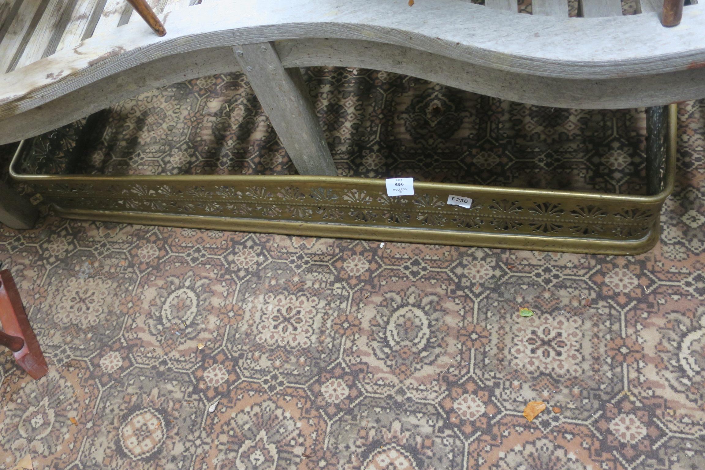 Lot 656 - A 19TH CENTURY BRASS FENDER with pierced frieze