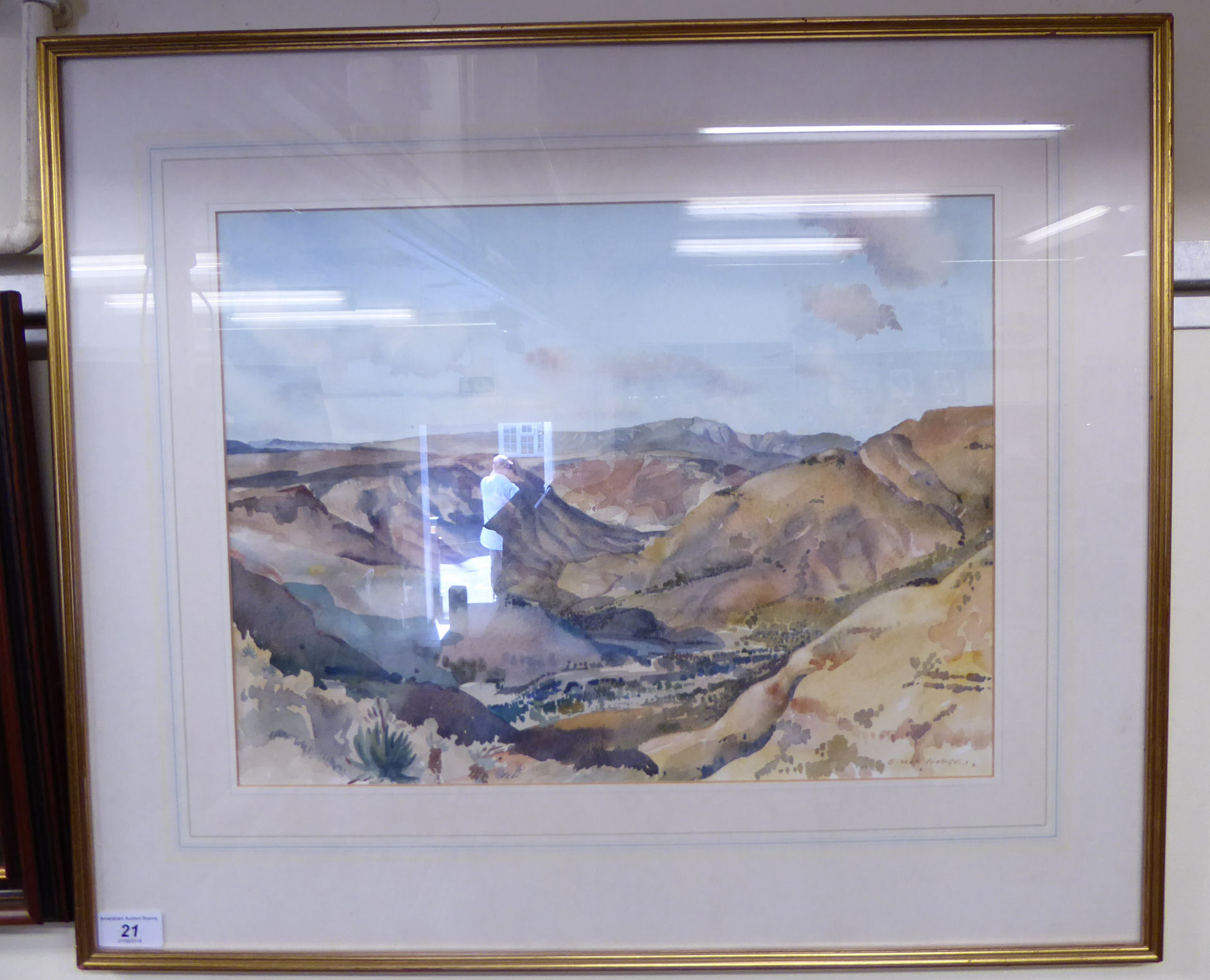Lot 21 - Simon Hodges - a landscape with a valley and mountains beyond watercolour bears a signature 16''